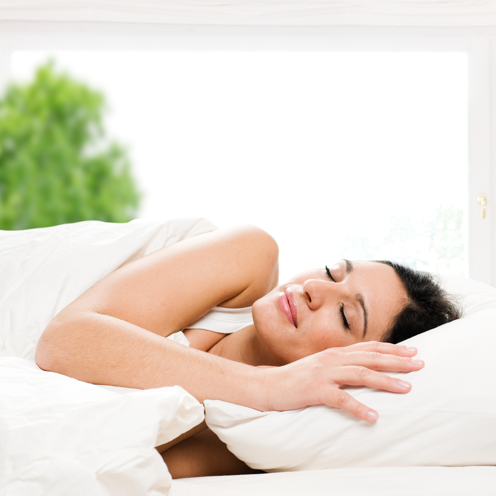 Beautiful young woman sleeping on bed in her bedroom at home in