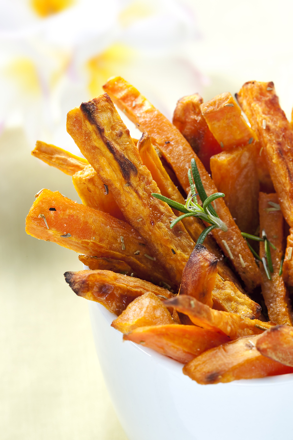 Sweet potato fries with rosemary oven-baked ready for snacking. Shallow depth of field.