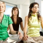 Young businesswomen sitting in yoga position on meeting room table.