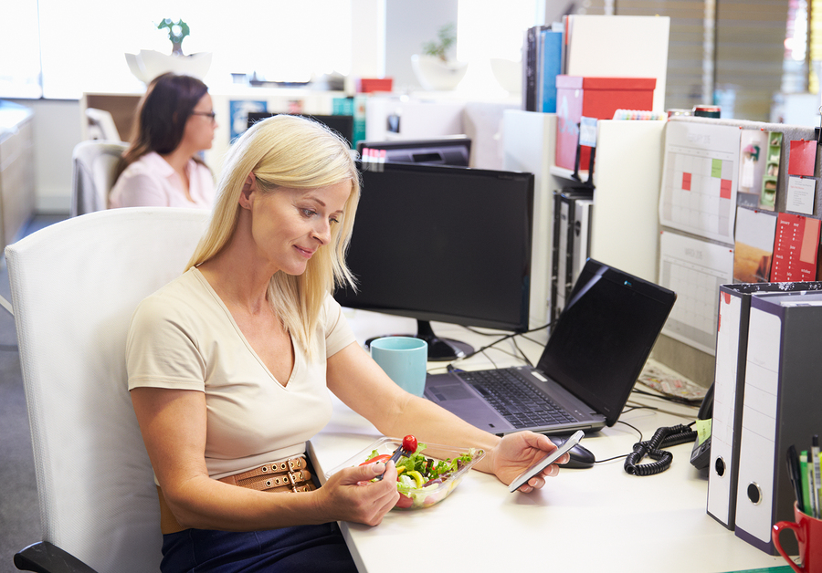 A working woman eating lunch using smart phone,phone at her desk