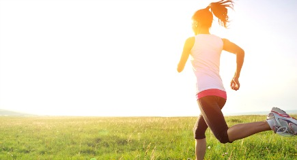 Runner athlete running on grass seaside. woman fitness sunrise/sunset jogging workout wellness concept.