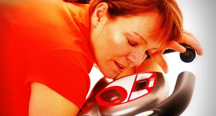 Woman sleeping on an exercise bike after training