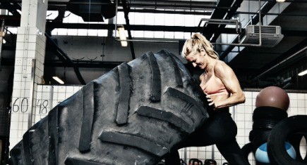 Fit female athlete working out with a huge tire turning and flipping in the gym. woman exercising with big tire.