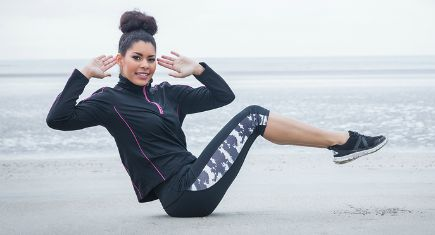 Fit girl working out on cold day at the beach