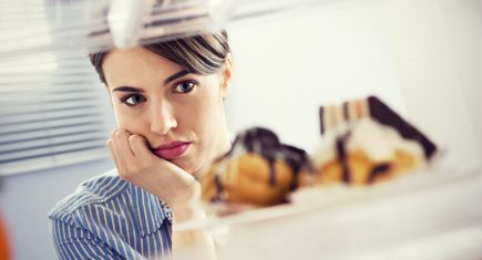 Young hungry woman in front of refrigerator craving chocolate pastries.