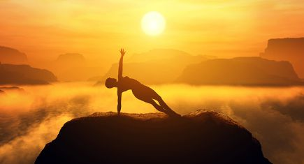 Woman meditating in side balance yoga position on the top of a mountains above clouds at sunset. Zen, meditation, peace