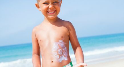 Adorable boy at tropical beach with sunblock cream.