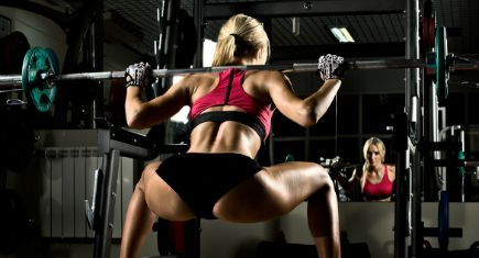 beautiful girl bodybuilder execute exercise with weight in dark gym