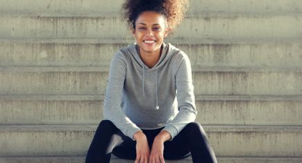 Portrait of a happy young african american sports woman sitting steps outdoors ** Note: Soft Focus at 100%, best at smaller sizes