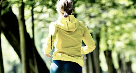 Woman runner running and walking in park summer nature exercising in bright forest outdoors