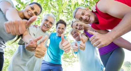 Happy athletic group with thumbs up on a sunny day