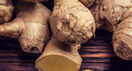 Raw ginger on a wooden background, studio shot