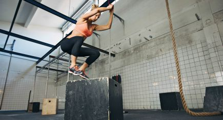 Fit young woman box jumping at a crossfit style gym. Female athlete is performing box jumps at gym. ** Note: Shallow depth of field ** Note: Visible grain at 100%, best at smaller sizes