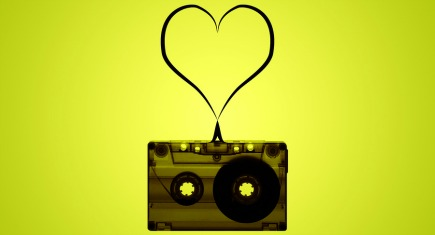 A cassette tape on a lime green and yellow background with tape coming out of the cassette to form a heart floating above the cassette.