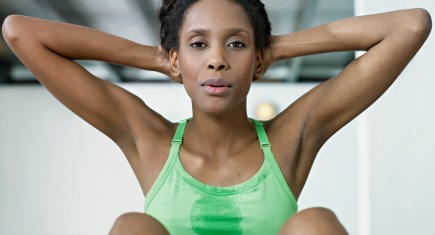 young african american woman in green sportswear exercising abdominals in fitness club looking at camera. Horizontal shape front view waist up