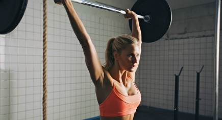Strong woman lifting barbell as a part of crossfit exercise routine. Fit young woman lifting heavy weights at gym. ** Note: Shallow depth of field ** Note: Visible grain at 100%, best at smaller sizes