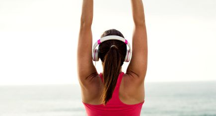 Female athlete stretching arms and back for warming up before fitness workout towards the sea. Sporty girl exercising at beach on summer wearing headphones.