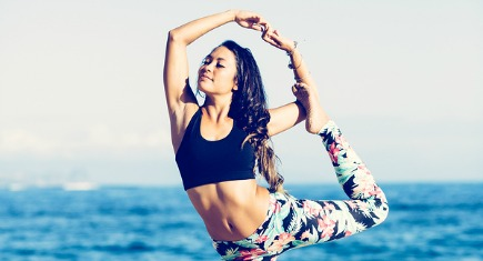 Sexy Young Woman Practicing Yoga on the Beach