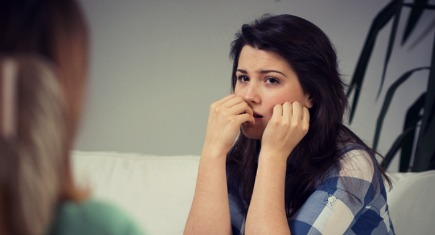 Worried girl biting her nails during psychotherapy session