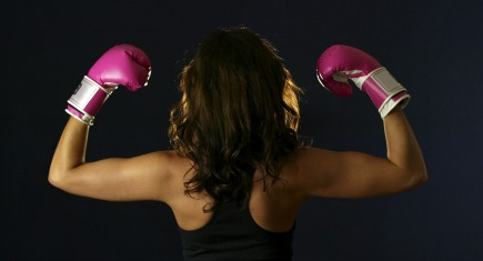 Young woman flexing with pink boxing gloves.