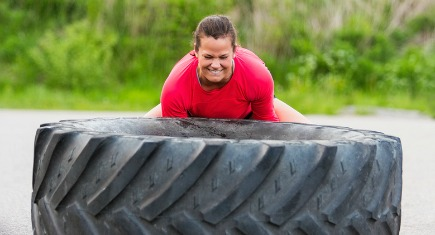 Dedicated woman lifting large tractor tire outdoors
