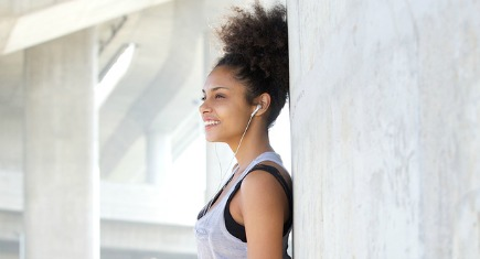 Portrait of a young fitness woman smiling outdoors with headphones