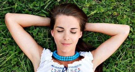 young woman lying down on grass with eyes closed