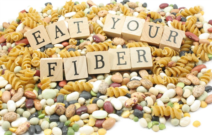 Assorted beans and whote wheat pasta mound with the words eat your fiber on wooden blocks placed on top