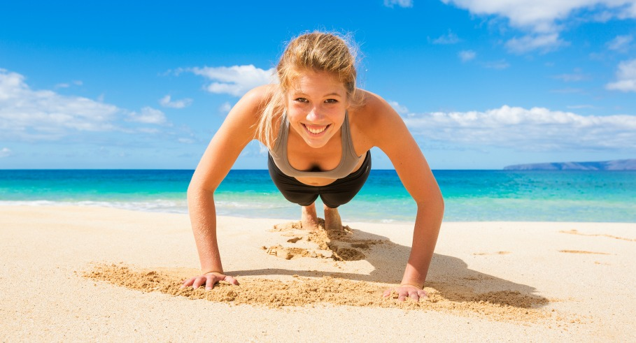 Attractive Young Woman Doing Push Up Exercise on the Beach???