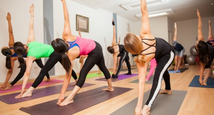Large group of people holding the triangle pose during a yoga class at a gym
