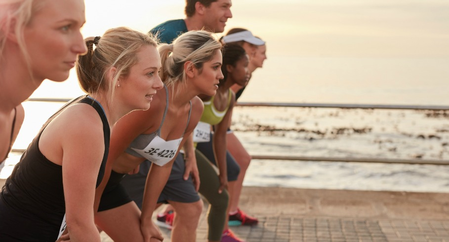 Runners standing on the line at the start of a race. Group of young people training for marathon race on road by the sea.