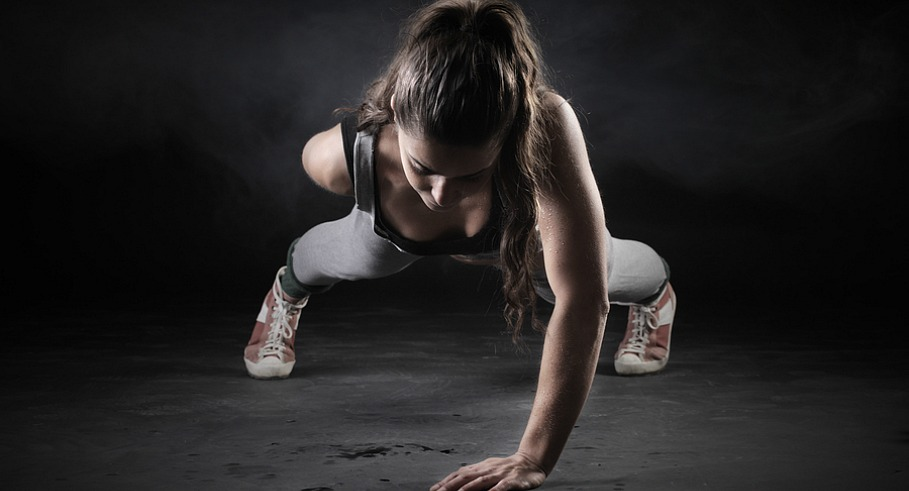 Young Woman Doing Push-Ups on dark background