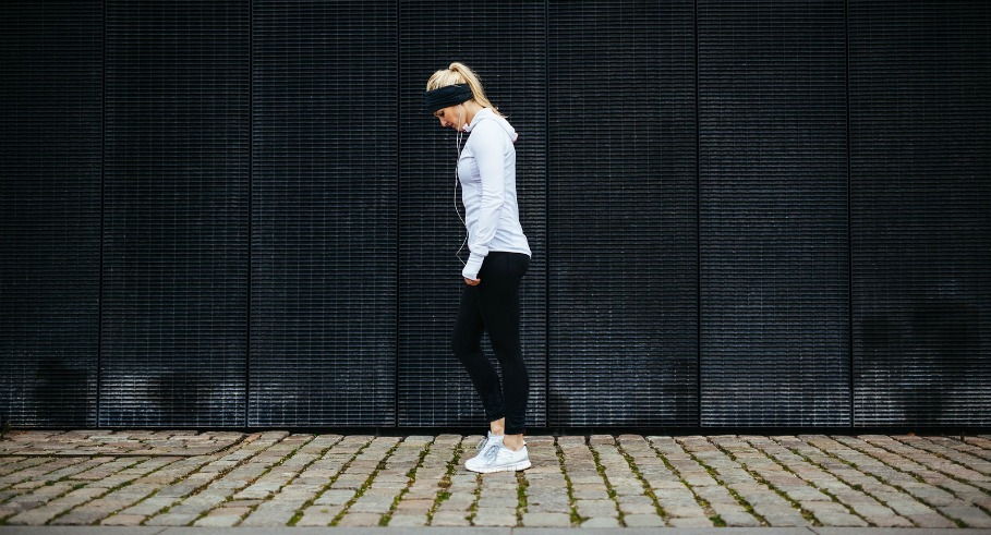 Side view of fitness woman preparing for a city run. Young caucasian woman walking on pavement looking down.