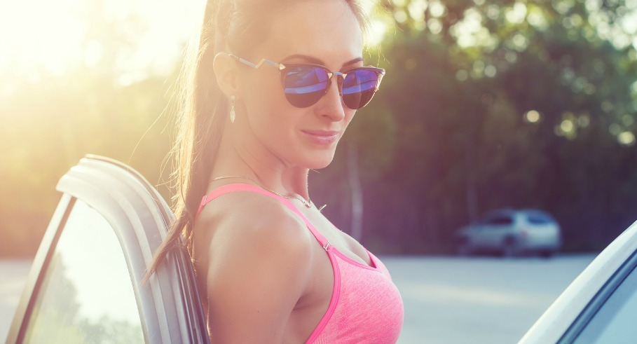 Athlete sporty fit young woman in sports bra wearing sunglasses standing leaning on car with door open looking at camera