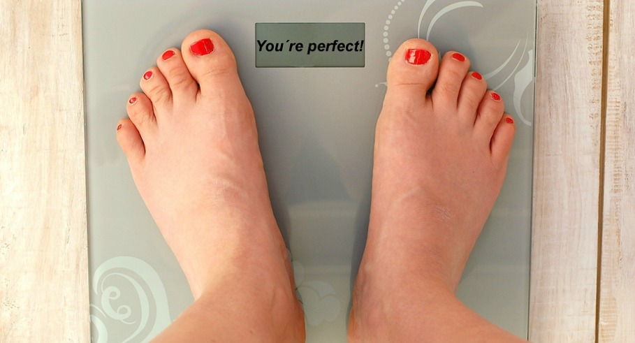 Feet on scales with text you look perfect in English language on the wooden background.Beaty and weight.Nice look and obesity in.