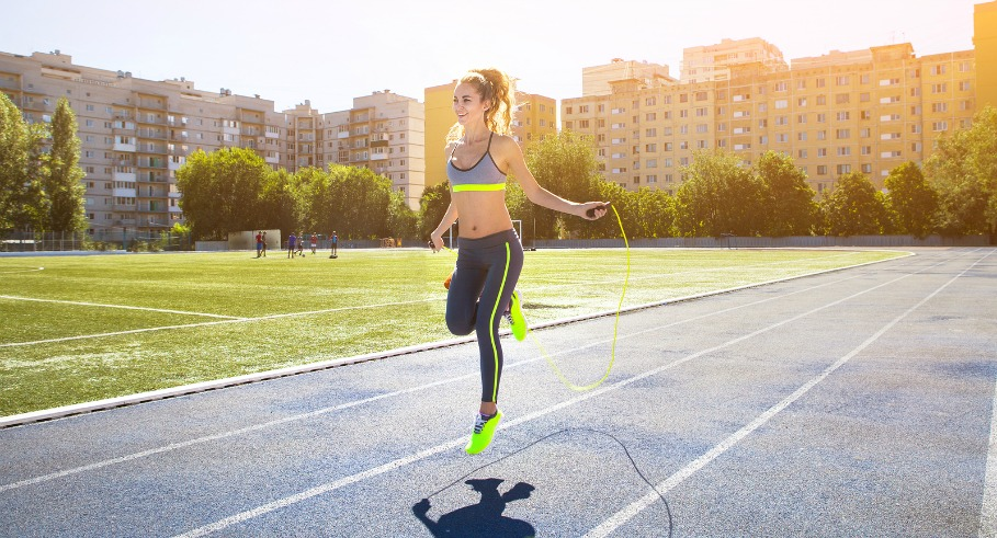 Woman with jumping rope. Beautiful young woman with a jumping rope in her hands with a stadium as background ** Note: Visible grain at 100%, best at smaller sizes