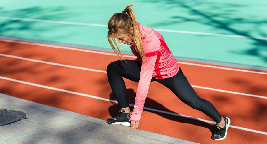 Portrait of a fitness woman doing stretching exercises at stadium