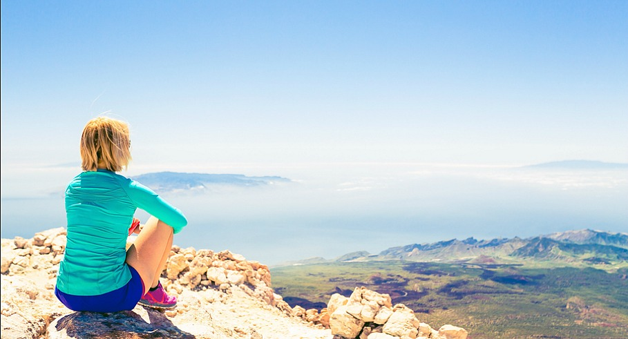 Young woman looking and meditation outside natural beautiful inspirational landscape environment fitness and exercising motivation and inspiration in sunny mountains over blue sky and ocean sea.