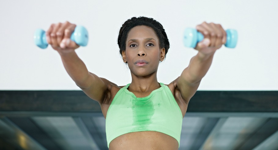 young african american woman in green sportswear doing weight lifting in fitness club. Horizontal shape front view waist up