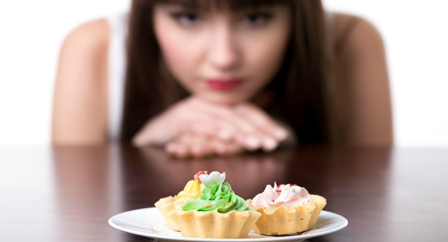 Young dieting woman sitting in front of plate with delicious cream tart cakes looking at forbidden food with unhappy and hungry expression studio white background isolated close-up