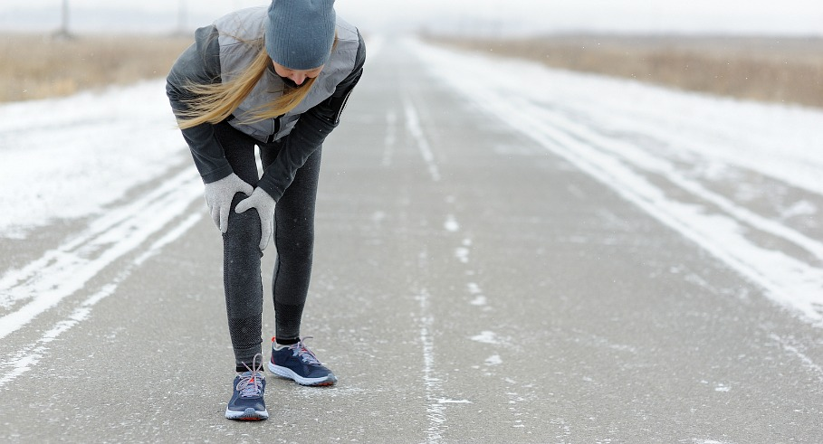 Injuries - sports running knee injury on woman. Winter marathon