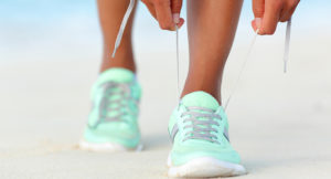 Runner woman tying laces of running shoes preparing for beach jo